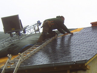 roofer on ladder fixing roof