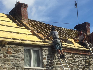 roofer on ladder repairing roof