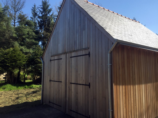 wood garage building with a slate roof